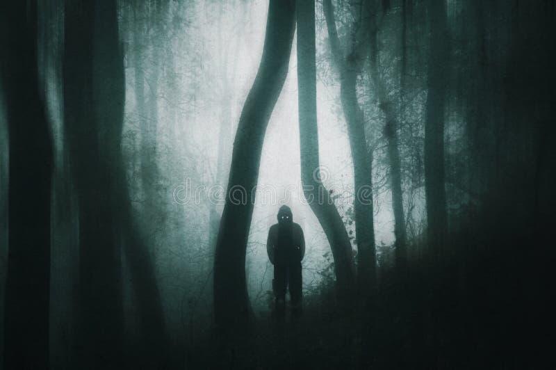 Uma figura mostrada em silhueta, encapuçado assustador com olhos de incandescência em uma floresta escura com um grunge silenciad imagens de stock
