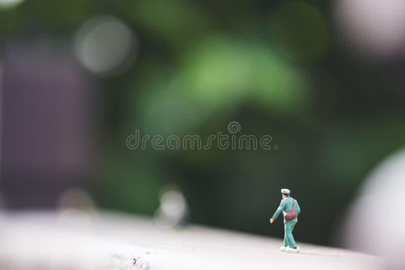Uma figura pequena do modelo do soldado no assoalho de madeira com fundo da natureza do verde do borrão imagem de stock