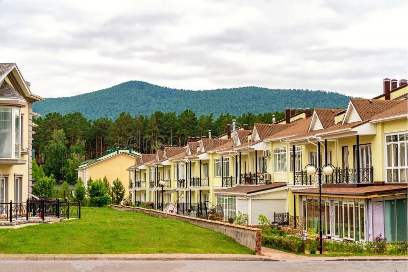 Uma fileira apenas de condom?nios amarelos novos terminados Vila residencial no pé das montanhas foto de stock royalty free