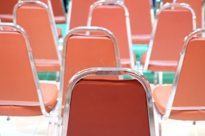 Uma fileira de cadeiras modernas alaranjadas no salão de exposição com o assoalho verde borrado imagens de stock