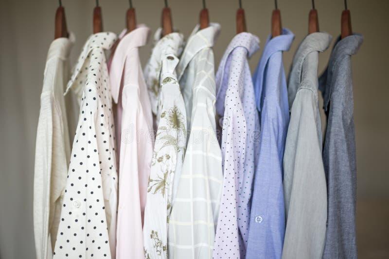Uma fileira de camisas sortidos do negócio para mulheres em ganchos em um armário foto de stock royalty free