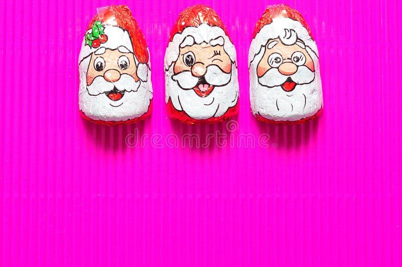 Uma fileira de com cobertura em chocolate com Santa Claus enfrenta envoltórios fotos de stock royalty free