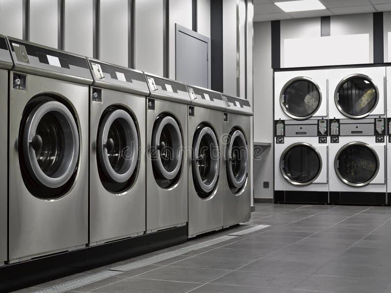 Uma fileira de máquinas de lavar industriais imagem de stock
