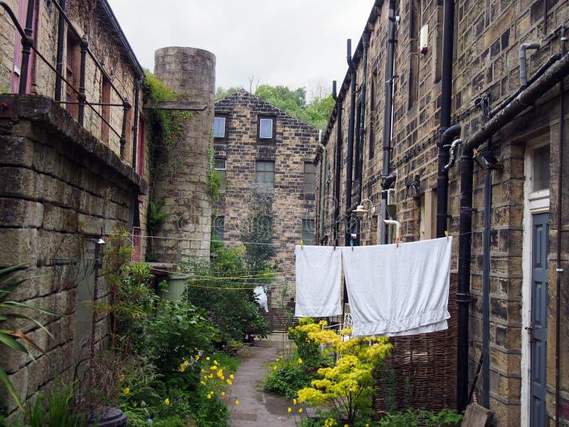uma fileira de típicas casas tradicionais de pedra do yorkshire numa pequena rua aterrada com flores de jardim e lavagem numa lin imagem de stock