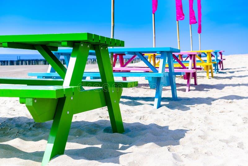 Uma fileira de tabelas de madeira coloridas em uma praia vazia Conceito do verão Arrendamentos das férias recuo Mola Terapia da n imagem de stock