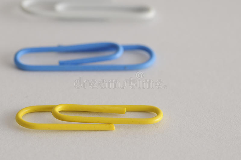 Uma fileira dos clipes de papel com o somente um no foco foto de stock