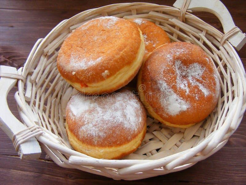 Uma filhós berlinesa fresca e saboroso na cesta do pão no vintage woodentable fotos de stock royalty free