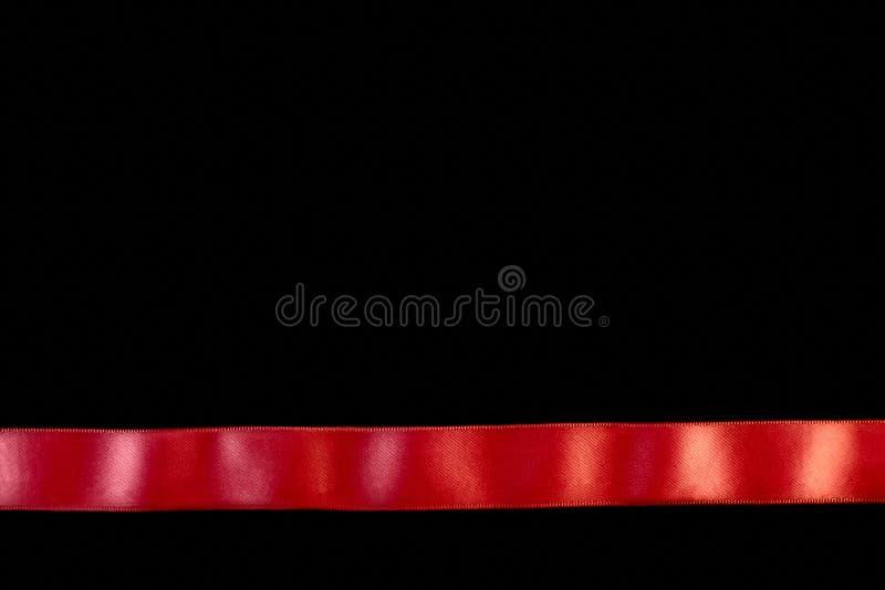 Uma fita horizontal vermelha isolada no preto fotografia de stock royalty free