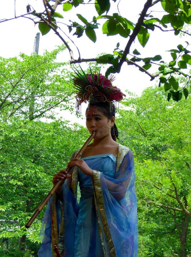 Uma flauta de bambu blowning vestida da mulher foto de stock royalty free