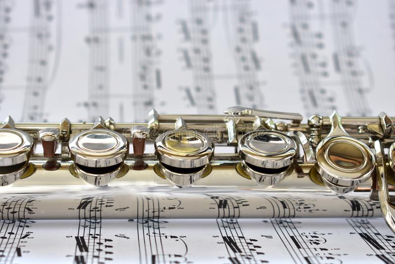 Uma flauta de prata na partitura fotografia de stock