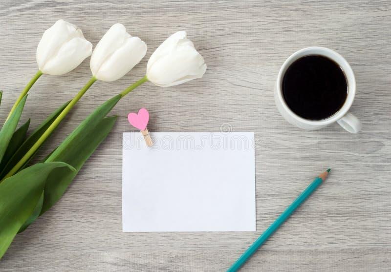 Uma folha de papel com uma pena vermelha, as flores e uma x?cara de caf? encontra-se em uma tabela de madeira branca Deixe uma no fotos de stock royalty free