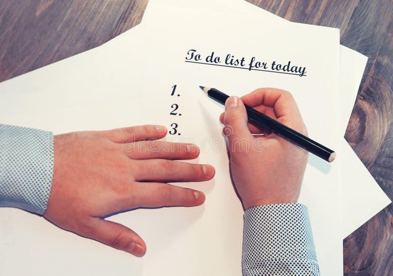 Uma folha de papel na frente de um homem com as palavras: Para fazer a lista para hoje Planeamento dos casos para o dia O conceit imagem de stock royalty free
