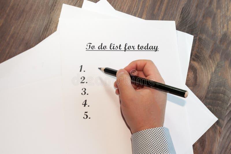 Uma folha de papel na frente de um homem com as palavras: Para fazer a lista para hoje Planeamento dos casos para o dia O conceit fotografia de stock