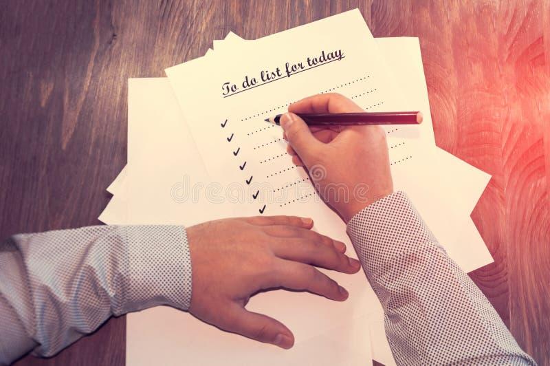 Uma folha de papel na frente de um homem com as palavras: Para fazer a lista para hoje Planeamento dos casos para o dia O conceit foto de stock royalty free