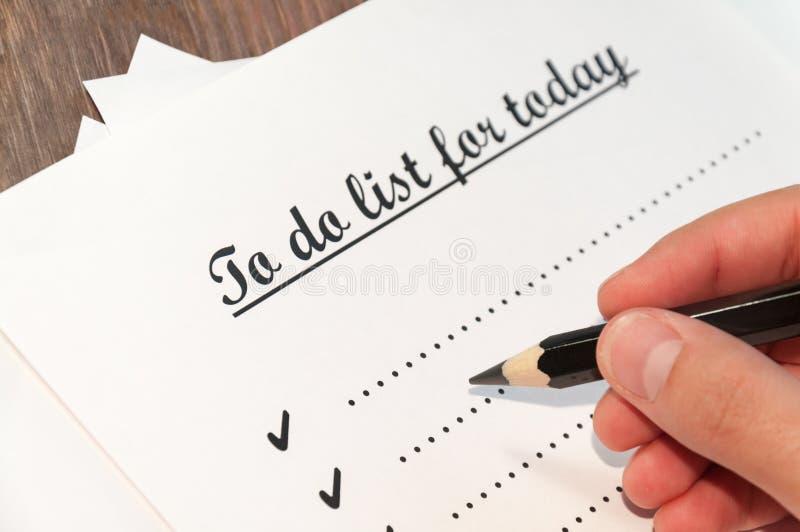 Uma folha de papel na frente de um homem com as palavras: Para fazer a lista para hoje Planeamento dos casos para o dia O conceit imagens de stock royalty free
