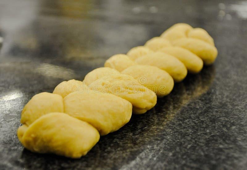 Uma forma bonita da trança do pão prepara-se para cozinhar e venda em uma loja da padaria imagens de stock