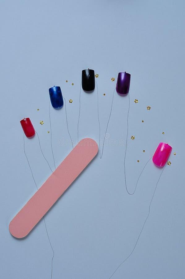 Uma forma da mão com pregos artificiais em cores diferentes e em um arquivo de prego fotos de stock royalty free
