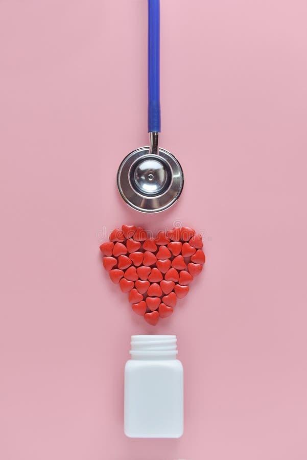 Uma forma do coração dos comprimidos da medicina que derramam fora da garrafa e do estetoscópio brancos no fundo cor-de-rosa Conc foto de stock