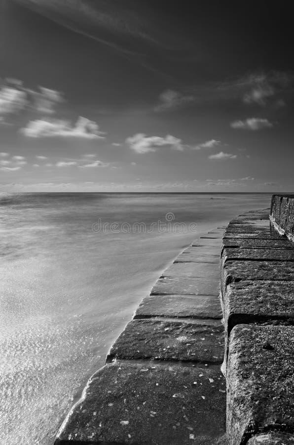 Escadas do mar em contacto com o seawater em preto e branco fotos de stock