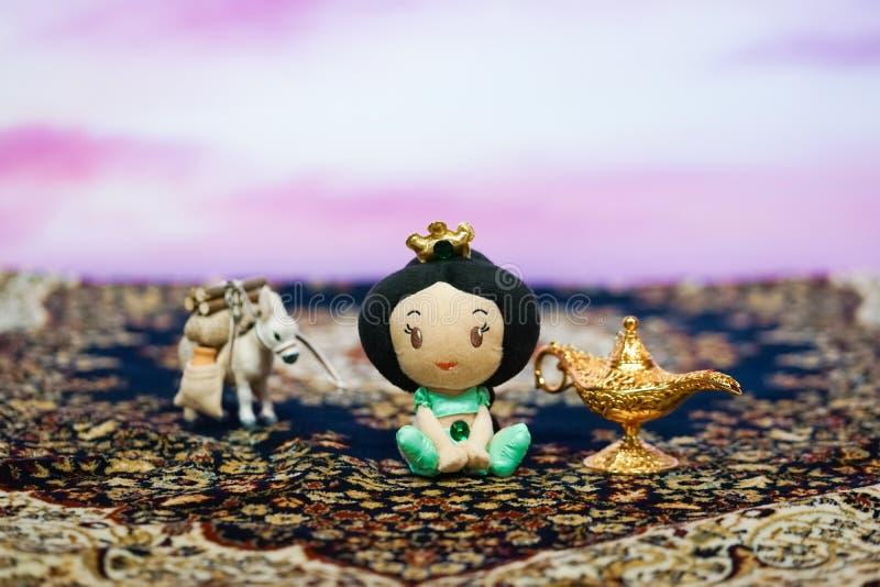 Uma foto da boneca do luxuoso do bebê da princesa Jasmine, da lâmpada de Aladim e de um animal do asno no carpe mágico foto de stock royalty free