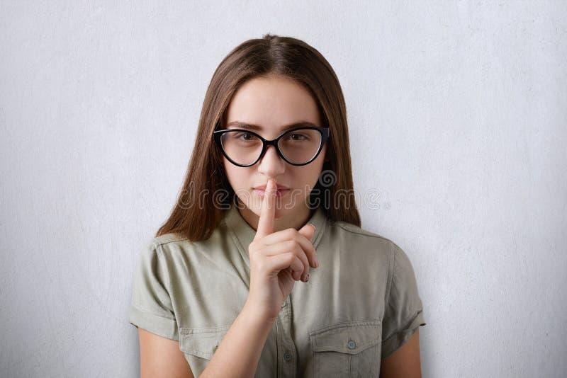Uma foto da menina atrativa séria com os vidros vestindo do cabelo reto escuro e da cara segura que põem seu dedo sobre a boca st imagens de stock royalty free