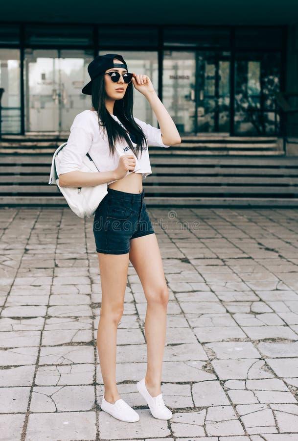 Uma foto da rua de um t-shirt branco vestindo da fêmea bonita nova e de um short preto das calças de brim que estão no fundo velh imagens de stock
