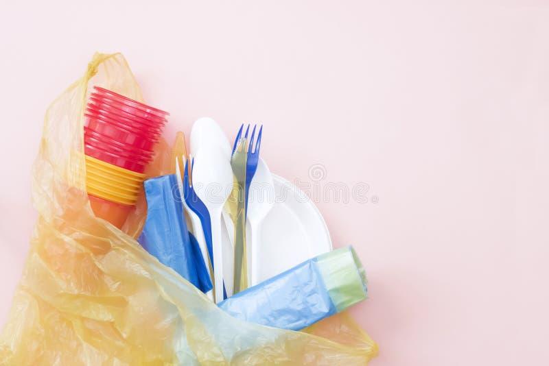 Uma foto de cima dos utensílios de mesa, das colheres, das forquilhas, dos copos e dos sacos descartáveis plásticos Desperdício z foto de stock