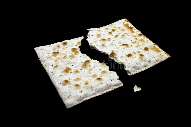Uma foto de duas partes de matzah ou de matza isoladas no fundo preto Matzah para os feriados judaicos da páscoa judaica Lugar pa fotos de stock royalty free