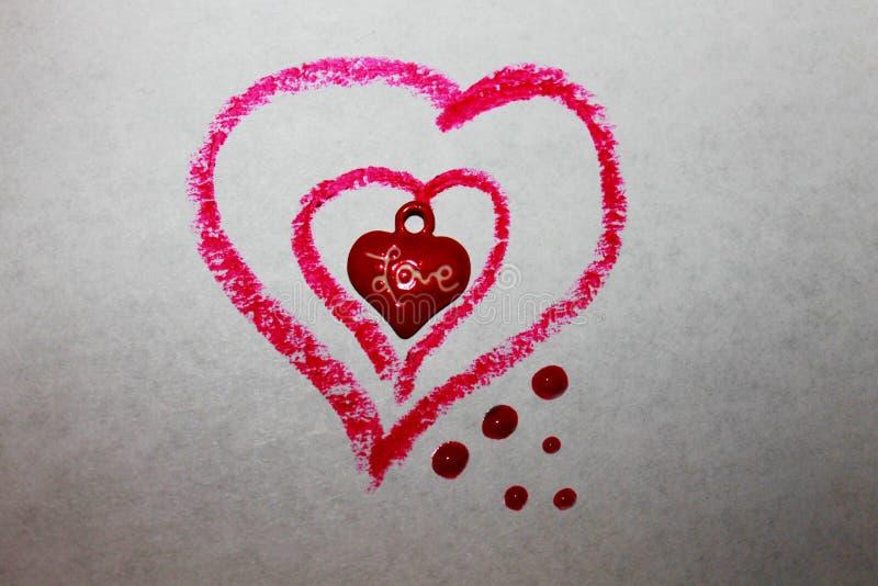 Uma foto de três corações pequenos no vermelho grande imagem de stock royalty free