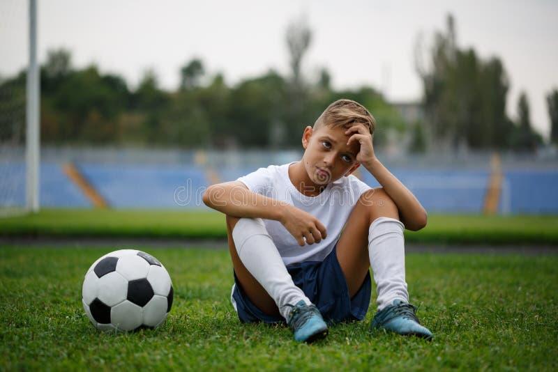 Uma foto de um menino desportivo com uma bola que senta-se em um campo verde em um fundo do estádio Atividades, conceito do passa foto de stock