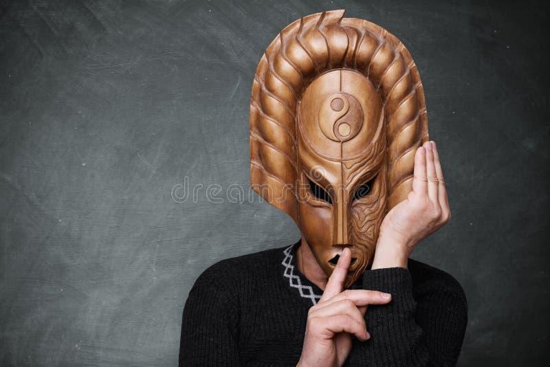 Uma foto do homem que está a máscara vestindo de yang do yin do fundo próximo da placa de giz que mostra o sinal do silêncio Um h imagem de stock