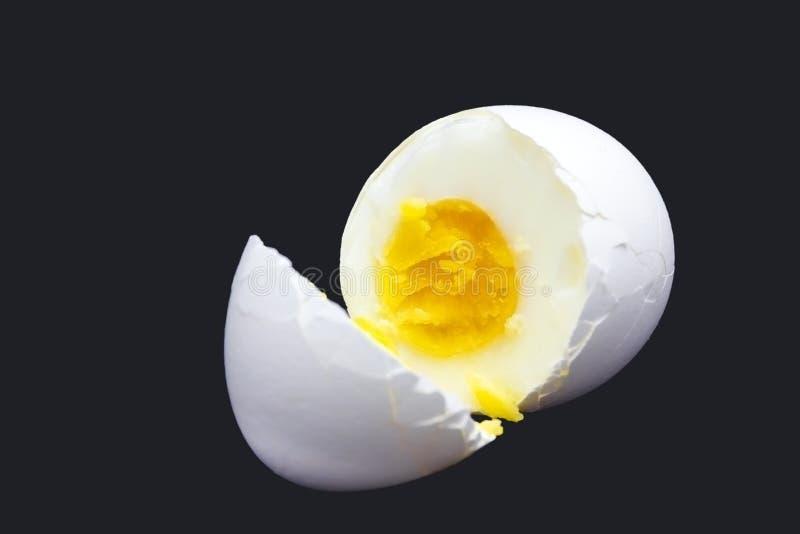 Uma foto do ovo branco quebrado fervido isolado na obscuridade - azul da galinha Egg a foto da gema do ` s, contraste brilhante d imagens de stock royalty free
