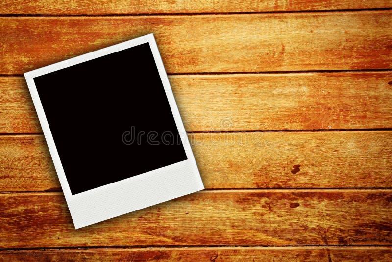 Uma foto do polaroid no fundo de madeira imagens de stock royalty free