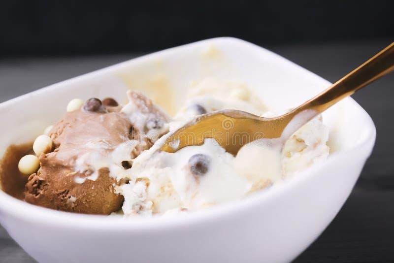Uma foto do processo de interromper uma bola do gelado de derretimento Gelado de baunilha com chocolate e migalhas com sp do cobr imagem de stock