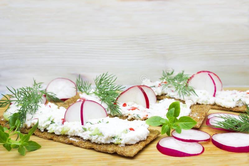 Uma foto dos biscoitos, do brinde torrado do pão de centeio com o requeijão decorado com rabanete, do pepino, do aneto e da manje foto de stock royalty free