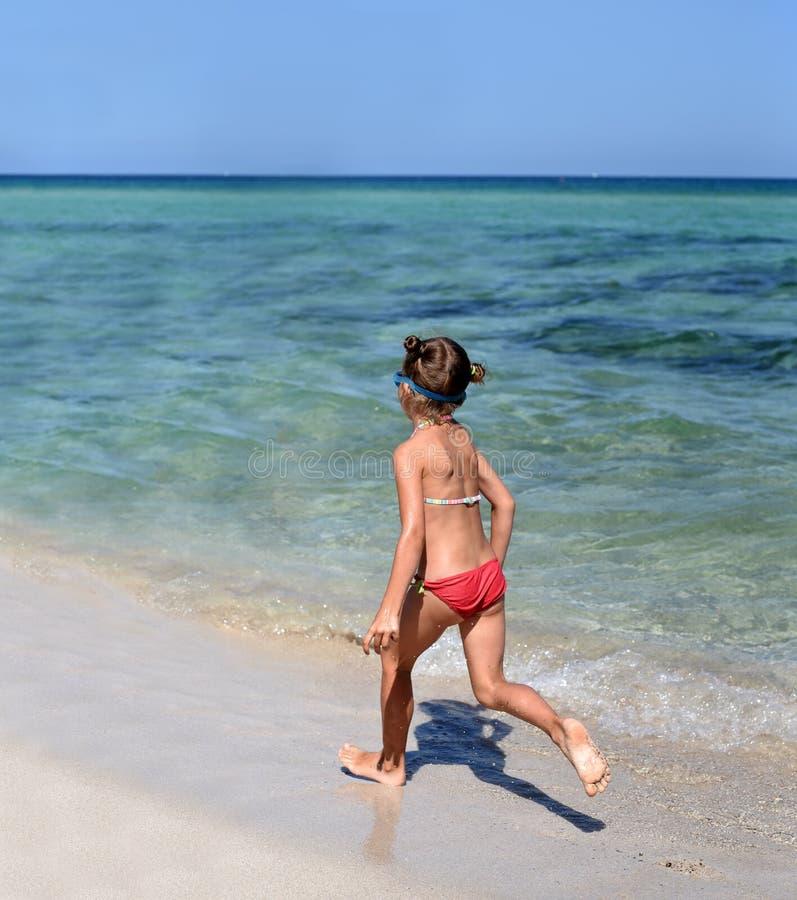 Uma foto ensolarada de uma menina no biquini que corre ao longo de uma costa de mar fotografia de stock