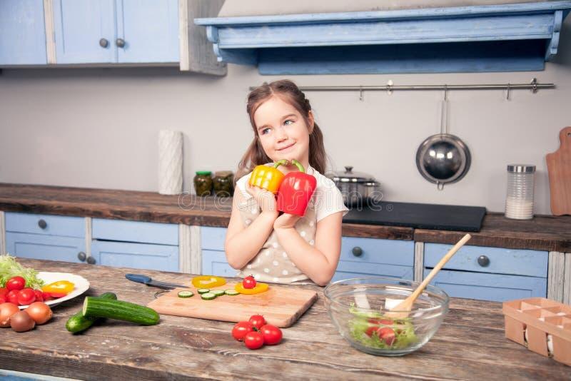 Uma foto horizontal de uma menina bonito que guarda uma pimenta búlgara imagens de stock