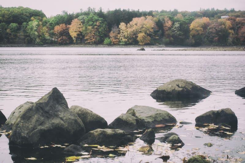 Uma foto retro do estilo do filme de um lago e de uma floresta new England na queda fotos de stock royalty free