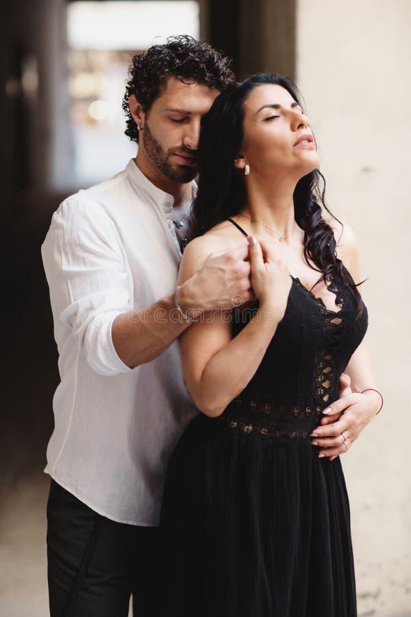 Uma foto sensual de um par novo O homem abra?a uma mulher Uma mulher em um vestido preto bonito fotos de stock royalty free