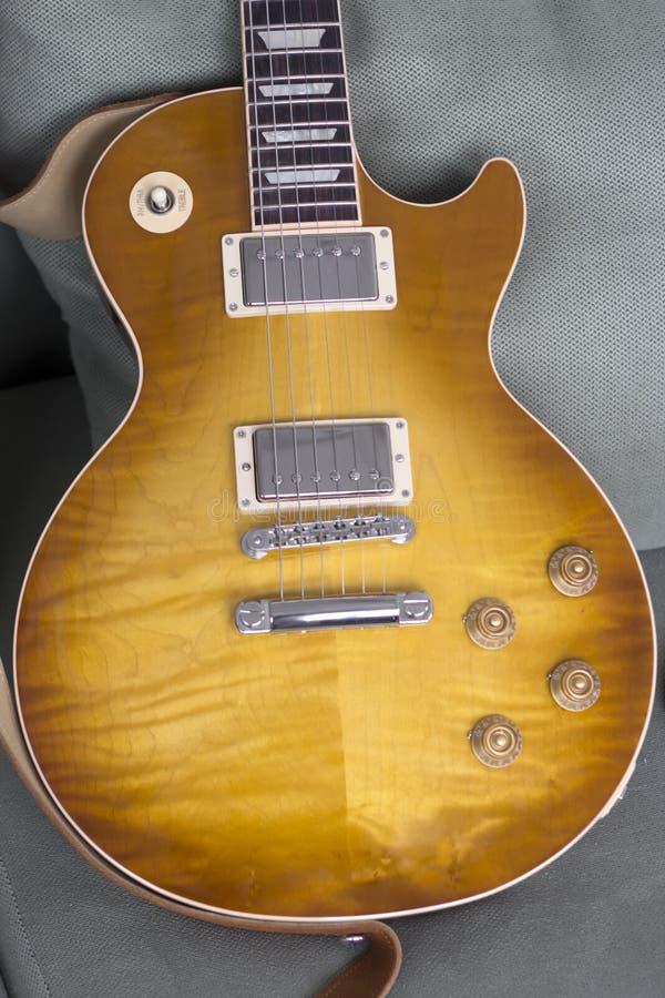 Uma foto simples de uma guitarra elétrica essa descansa em um sofá verde fotografia de stock