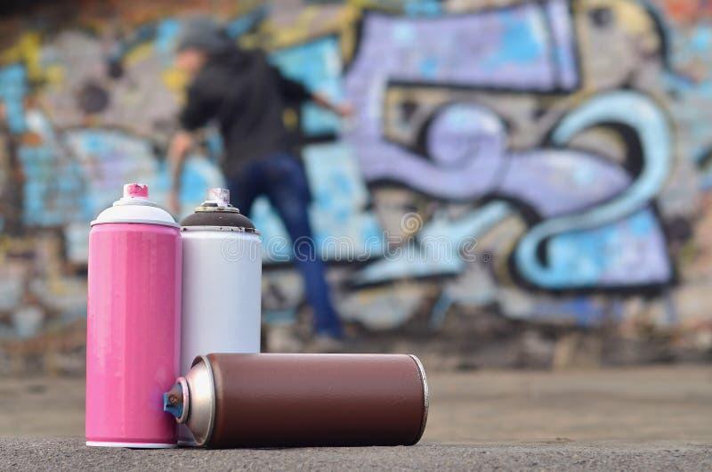 Uma fotografia de um determinado número de latas da pintura contra o graf fotos de stock
