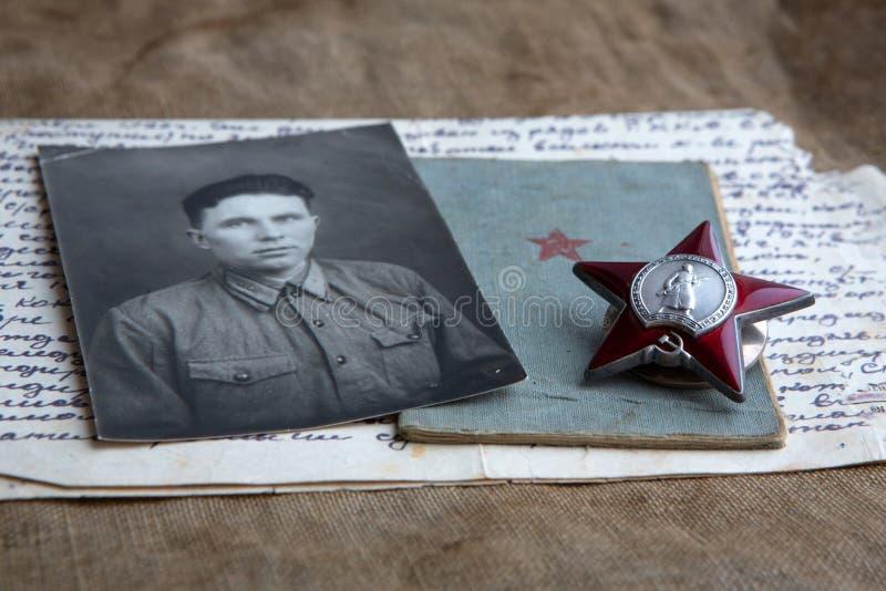 Uma fotografia de um homem no uniforme militar está encontrando-se ao lado da ordem de Red Star da URSS e de um livro militar Let imagens de stock