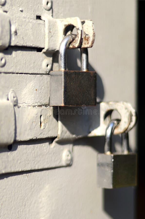 Uma fotografia do fragmento é uma porta do metal com os dois cadeado quadrados Foco seletivo com profundidade de campo rasa foto de stock royalty free