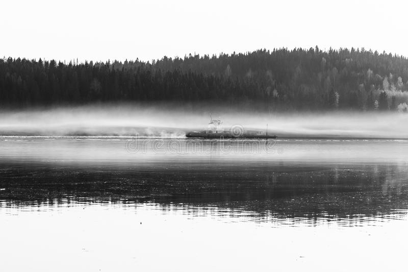 Uma fotografia preto e branco de como um navio de carga navega em uma névoa imagem de stock royalty free