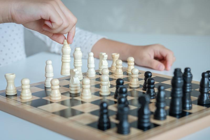 Uma garota aprende a jogar xadrez foto de stock