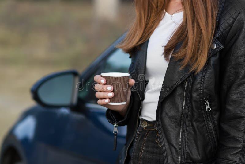 Uma garota com uma xícara de chá inclinada em um carro Conceito de cultura do café imagem de stock