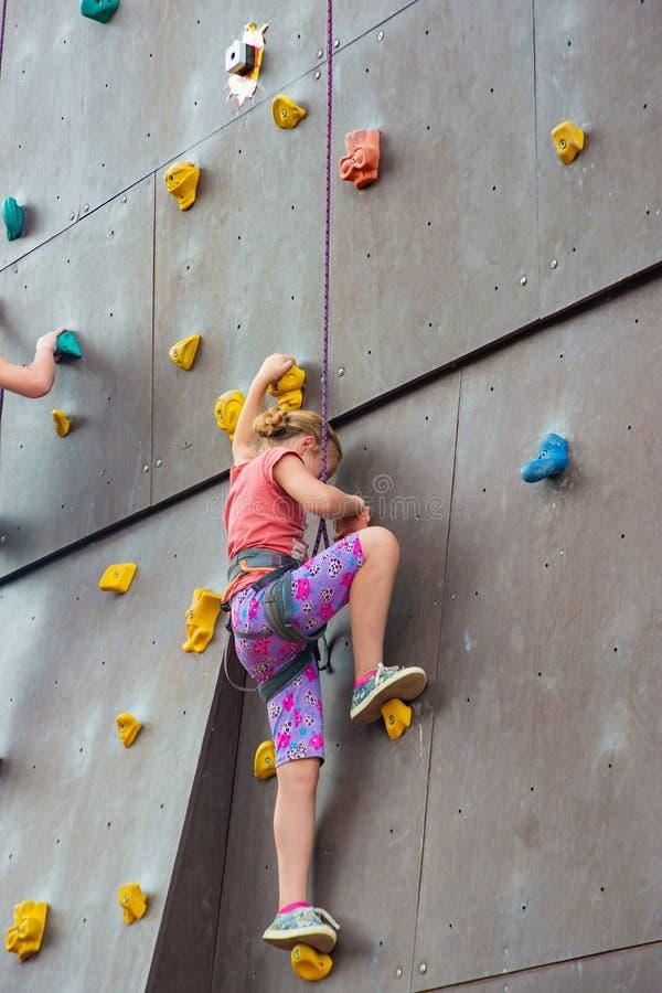 Uma garota invade uma torre artificial escalada com seguro em um parque esportivo extremo imagem de stock royalty free