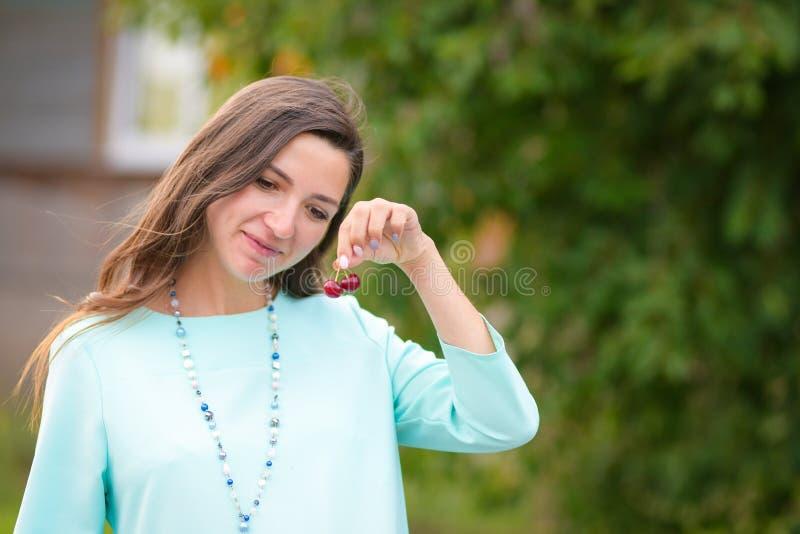 Uma garota que adora cerejas Retrato de uma linda jovem que guarda cereja em suas mãos e sorri vitaminas pré-natal imagem de stock