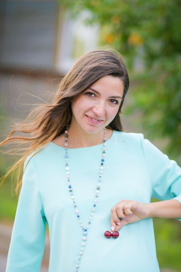 Uma garota que adora cerejas Retrato de uma linda jovem que guarda cereja em suas mãos e sorri vitaminas pré-natal imagem de stock royalty free