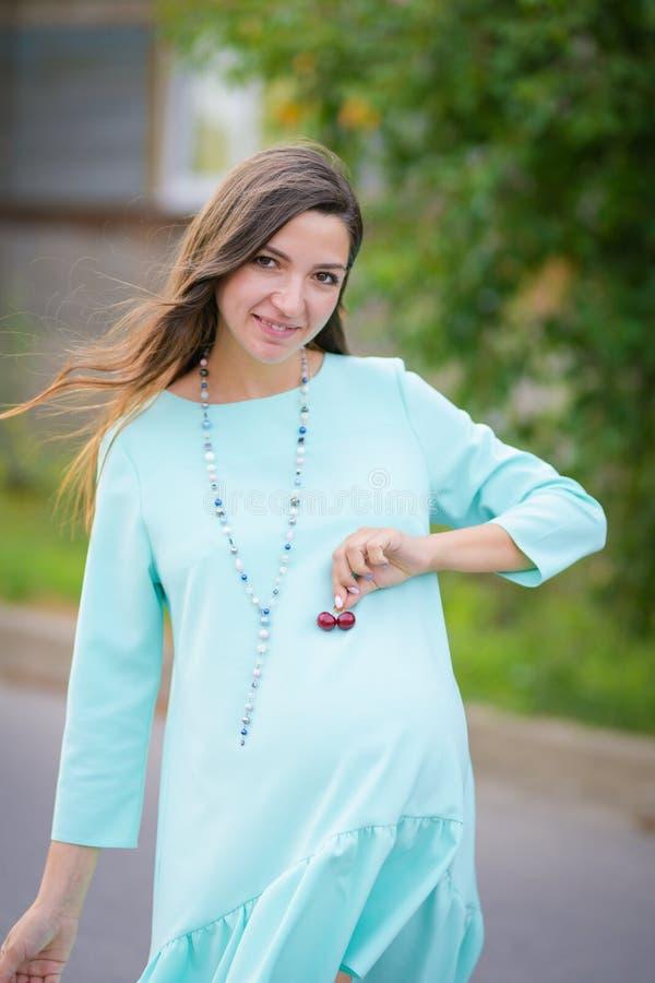 Uma garota que adora cerejas Retrato de uma linda jovem que guarda cereja em suas mãos e sorri vitaminas pré-natal fotografia de stock